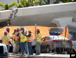Workers wait near a section of a collapsed pedestrian bridge, March 16, 2018, near Florida International University in the Miami area. The pedestrian bridge, which was under construction, collapsed onto a busy Miami highway Thursday, crushing vehicles beneath it.