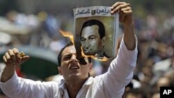 បុរសម្នាក់ដុតកម្ទេចរូបថតប្រធានាបធិបតីអេហ្ស៊ីបដែលត្រូវបានបណ្តេញចេញពីអំណាច ក្នុងកំឡុងពេលបាតុកម្មតវា នៅ Tahrir Square ក្រុង Cairo កាលពីថ្ងៃទី១ ខែកក្កដា ២០១១។