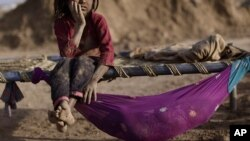 Pakistani Naginah Sadiq, 5, who works in a brick factory, rests on a bed next to her sister Shahzadi, 8 months, on World Day Against Child Labor, on the outskirts of Islamabad, Pakistan, June 12, 2012.