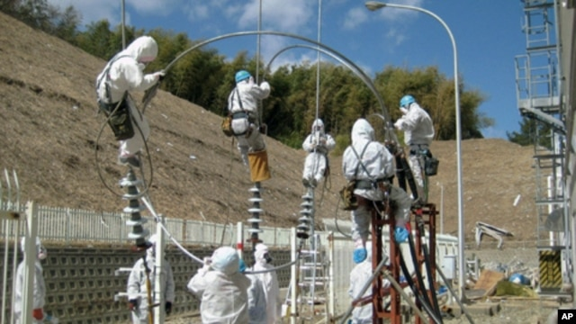 Workers attempt to repair power lines at the Fukushima Daiichi Nuclear Power Plant in Tomioka, Japan, March 24, 2011