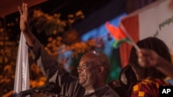 FILE - Roch Marc Kabore, winner of Burkina Faso's presidential election, celebrates as supporters gather outside his campaign headquarters in Ouagadougou, Dec. 1, 2015.