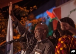 Roch Marc Christian Kabore, left, winner of Burkina Faso's presidential election, celebrates as supporters gather outside his campaign headquarters in Ouagadougou, Dec. 1, 2015.