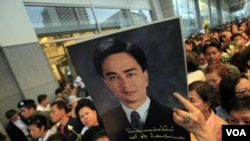 Pendukung partai Demokrat di Thailand membawa poster Abhisit Vejjajiva dalam kampanye di Bangkok (23/6).