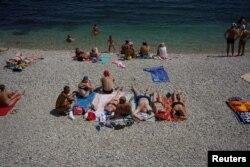 People sunbathe on a beach in Koktebel, southern Crimea, July 23, 2016.