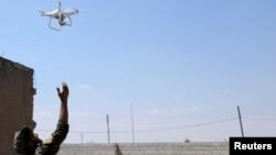 مغربی رقہ میں امریکی حمایت یافتہ ڈیموکریٹک فورس کا ایک اہل کار ڈرون اڑا رہا ہے۔ 18 جون 2017
