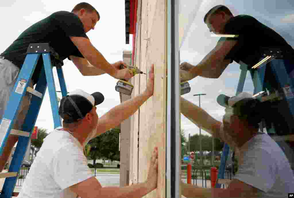 Justin Davis, left, and Brock Mclean board up a business in advance of Hurricane Michael in Destin, Florida, Oct. 9, 2018.