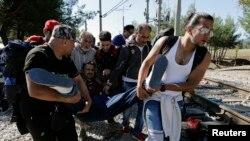 Des réfugiés syriens portent un des leurs compagnons tombé malade au cours de leur traversée de la Grèce à la Mécedoine, 12 septembre 2015.