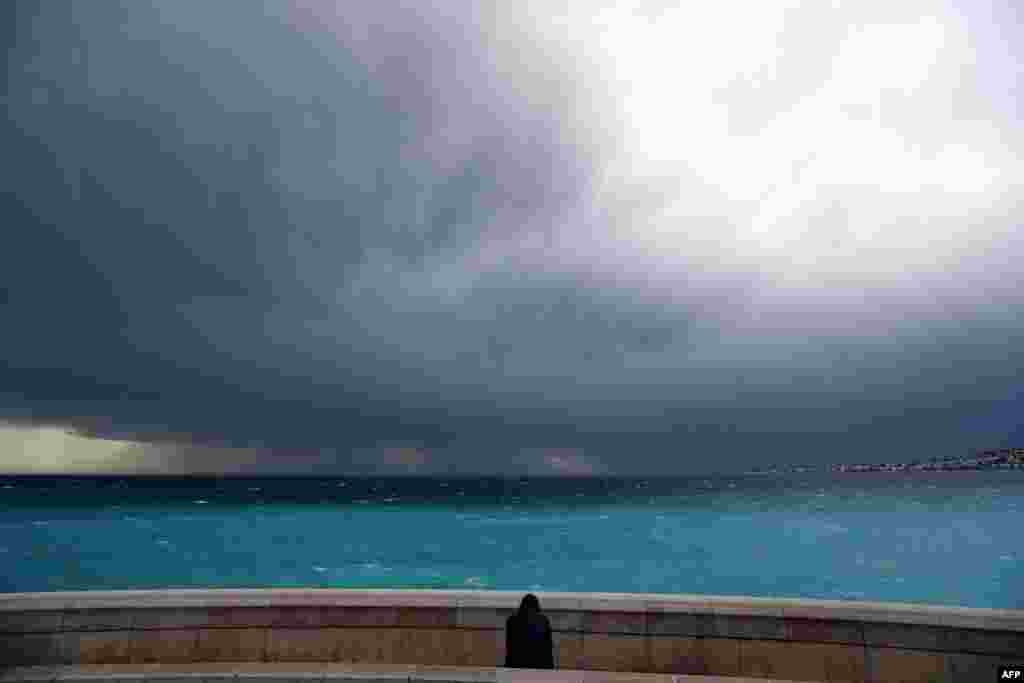 A man looks at an approaching storm in Nice, southeastern France.
