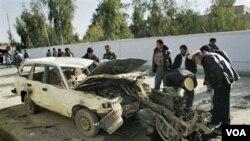 Dua polisi lalu lintas sedang memeriksa mesin mobil yang digunakan untuk serangan bunuh diri di Kandahar Selatan.