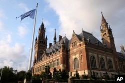 FILE - A United Nations flag flutters in the wind next to the International Court of Justice in the Hague, the Netherlands, Aug. 27, 2018.