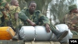 An M23 soldier rests on boxes of ammunition as the group withdraws from the Congolese city of Goma, Dec. 1, 2012 (photo - VOA/G. Joselow).