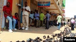 FILE - In an earlier tax protest, vendors sell used shoes on the street outside their shops in Kampala, Uganda, June 28, 2013.