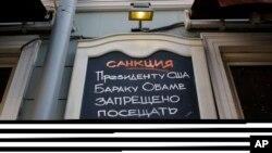 """Papan bertuliskan """"Sanksi. Presiden AS Barack Obama dilarang masuk Restoran Dolma!"""" di Moskow, Rusia, Maret 2014."""