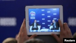 Russia's President Vladimir Putin (R) and Prime Minister Dmitri Medvedev are seen on the screen of a tablet computer during a meeting in the Moscow region, Oct. 3, 2013.