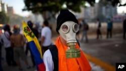 Un manifestante anti-gubernamental usa máscara de gas para protegerse en los enfrentamientos con la policía.