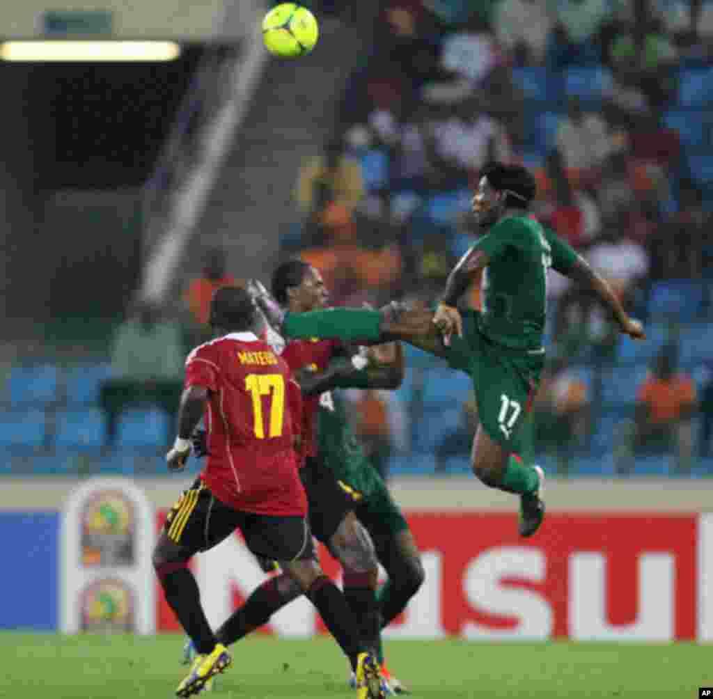 Paul Kebe Koulibaly, do Burkina Faso e Mateus Galiano disputam o esférico, durante o primeiro jogo das Palancas Negras, no CAN 2012, no Estádio de Malabo, a 22 de Janeiro