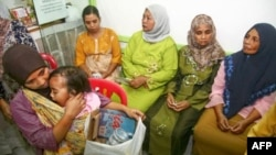 Seorang ibu menggendong anaknya sambil membawa sampah yang dapat didaur ulang di klinik Bumi Ayu, Malang, Jawa Timur. (AFP)