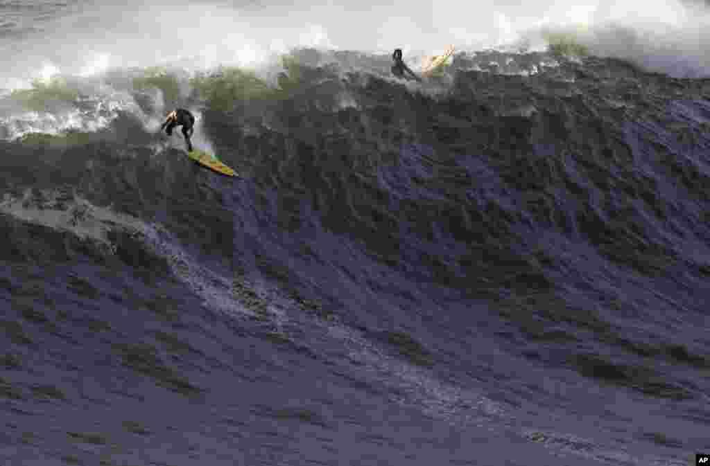US surfer Garrett McNamara, left, makes a take off on a wave at Praia do Norte beach in Nazare, Portugal, Jan. 29, 2013.