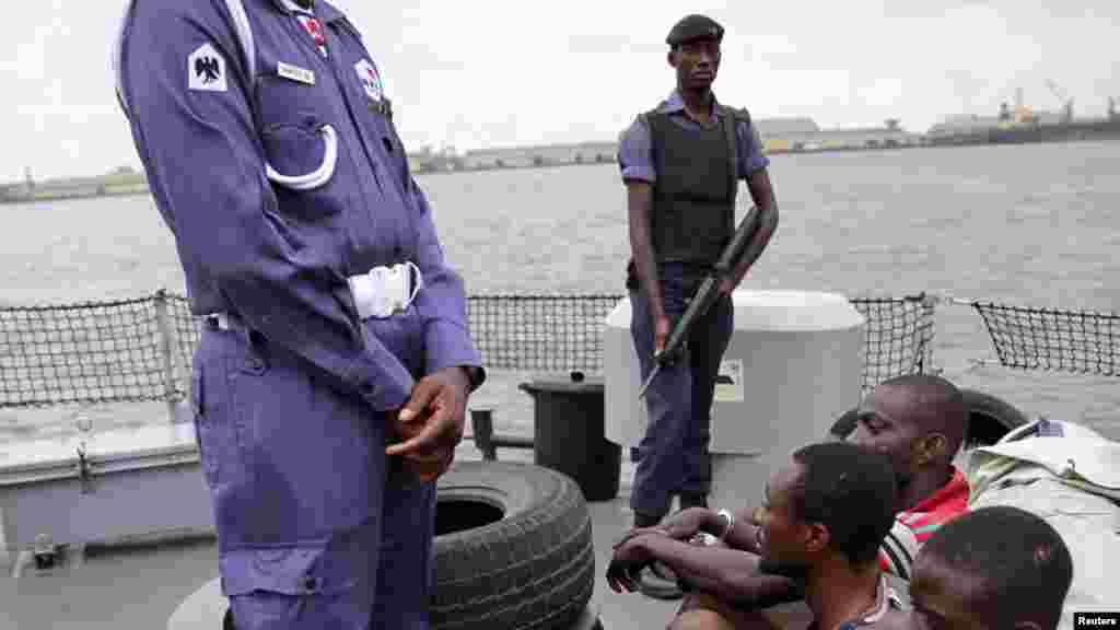 Naval police stand guard as suspected pirates are paraded aboard a naval ship after their arrest by the Nigerian Navy at a defence jetty in Lagos, August 20, 2013.