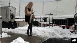 Seorang perempuan memeriksa telepon selularnya di luar Lincoln Center, tempat berlangsungnya acara mode New York's Fashion Week (9/2). (AP/Richard Drew)