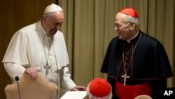ພະສັນຕະປາປາ Francis ໂອ້ລົມກັບ ພະສັງຄະລາດ Peter Erdo ຈາກ ຮັງກາຣີ ໃນຂະນະທີ່ພະອົງ ເດີນທາງຮອດບ່ອນປະຊຸມພາກເຊົ້າ ໃນການປະຊຸມທາງສາສະໜາ ຂອງພະສັງຄະລາດ ມື້ສຸດທ້າຍທີ່ນະຄອນ Vatican. 24 ຕຸລາ, 2015.