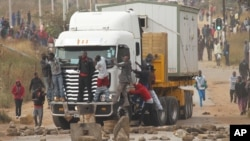FILE: Rioters cling to the front of a lorry as they clash with Zimbabwean police in Harare, Monday, July, 4, 2016. (AP Photo/Tsvangirayi Mukwazhi)
