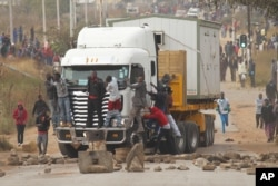 Rioters cling to the front of a lorry as they clash with Zimbabwean police in Harare, Monday, July, 4, 2016
