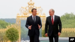 President Emmanuel Macron, left, and his Russian counterpart Vladimir Putin walk, as they meet for talks before the opening of an exhibition marking 300 years of diplomatic ties between the two countries at Palace of Versailles, May 29, 2017.