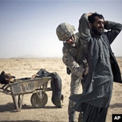 A US Army soldier searches an associate of a suspected Taliban IED placer, seen in a wheelbarrow, who was killed in a coalition missile strike in Zhari district, Kandahar province (File)