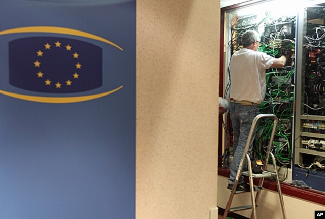 Communication technicians work at a phone and internet cable closet, at the European Council building in Brussels, July 1, 2013.