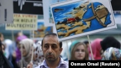 A man holds a poster with a drawing depicting drowned Syrian toddlers during a demonstration for refugee rights in Istanbul, Turkey, September 3, 2015. The distraught father of two Syrian toddlers who drowned with their mother and several other migrants a