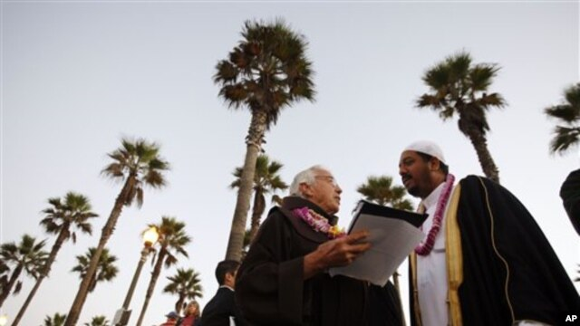 Rev. Christian Mondor, left, talks with Fawad Yacoob of the Islamic Society of Orange County at the Blessing of the Waves ceremony in Huntington Beach, California, a few years ago