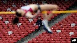 Một nhân viên bảo vệ nhìn nữ vận động viên nhảy cao Nga Elena Slesarenko tại sân vận động quốc gia của Trung Quốc, Bắc Kinh.