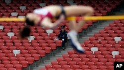 FILE - A security guard watches as a Russia athlete, front, makes an attempt at the women's high jump during the 2014 IAAF World Challenge Beijing held at China's National Stadium in Beijing, Wednesday, May 21, 2014.