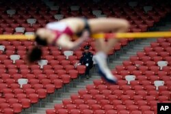 FILE – Observed by a security guard, a Russian athlete attempts the women's high jump during the IAAF World Challenge Beijing at China's National Stadium, May 21, 2014. The World Anti-Doping Agency has accused Russians of participating in a vast doping scheme.