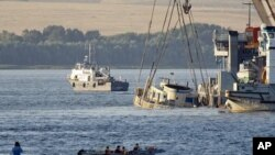 Cranes transport the Bulgaria sunken tourist boat, the upper deck of which is seen above the waters of the Volga river, during an operation, realized by Russian Emergencies Ministry, July 23, 2011