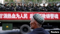 FILE - A Uighur man looks on as a truck carrying paramilitary policemen travel along a street during an anti-terrorism oath-taking rally in Urumqi, Xinjiang Uighur Autonomous Region.