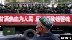 FILE - A Uighur man looks on as a truck carrying paramilitary policemen travel along a street during an anti-terrorism oath-taking rally in Urumqi, Xinjiang Uighur Autonomous Region.