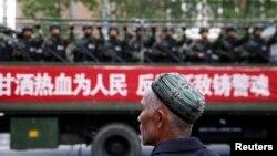 Seorang pria Uighur melihat truk berisi polisi paramiliter melintas di jalan di Urumqi, Xinjiang. (Foto: Dok)