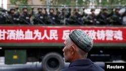 Một người Uighur nhìn theo chiếc xe tải chở cảnh sát bán quân sự chạy trên đường trong cuộc vận động chống khủng bố ở Urumqi, Tân Cương