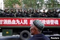 FILE - A Uighur man looks on as a truck carrying paramilitary policemen travels along a street during an anti-terrorism oath-taking rally in Urumqi, Xinjiang Uighur Autonomous Region.