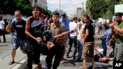 2014年8月3日,加沙地带南部的巴勒斯坦人在拉法一所联合国办的学校外抬着一名被炸死的人。