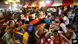 "FILE - In this Thursday, Oct. 22, 2015 photo, customers eat Bamee Jom Palang, or ""Power Noodles"", at one of the most crowded food stalls at Rotfai Market in Bangkok, Thailand. (AP Photo/Sakchai Lalit)"
