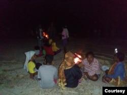 Warga komunitas adat Besipae, Rabu (19/8) duduk di atas tanah dengan penerangan api unggun sambil memeluk anak mereka yang tertidur. (Foto: Martheda Esterlina Selan)