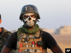 A member of Iraq's elite counterterrorism forces dons a mask for the advance on Mosul, Iraq, Oct. 20, 2016.