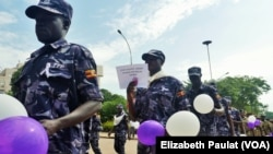 FILE - Ugandan Police hold balloons and signs condemning violence against women, Kampala, Uganda, Dec. 5, 2015.