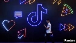 2019年10月18日行人走过杭州国际人工智能产品博览会上的TikTok应用程序标志。