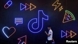 在杭州國際智能產品博覽會期間,一位男士拿著手機走過字節跳動公司的TikTok與抖音應用軟件的標識。 (2019年10月18日)