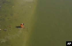 An Indian man washes his clothes in the Ganges River.