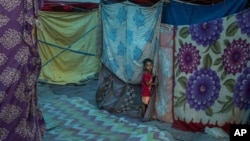 A young Rohingya refugee boy stands outside a tent at a refugee camp alongside the banks of the Yamuna River in the southeastern borders of New Delhi, sprawling Indian capital, July 1, 2021
